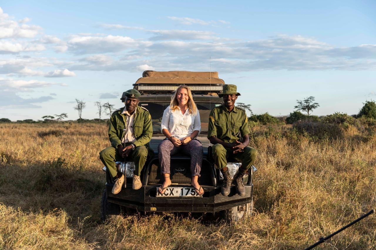 Liselott Lindström sitter på en motorhuv. Bilen är ute i torr savann. På båda sidorna har hon personer i gröna kläder som ser ut som viltvårdare.